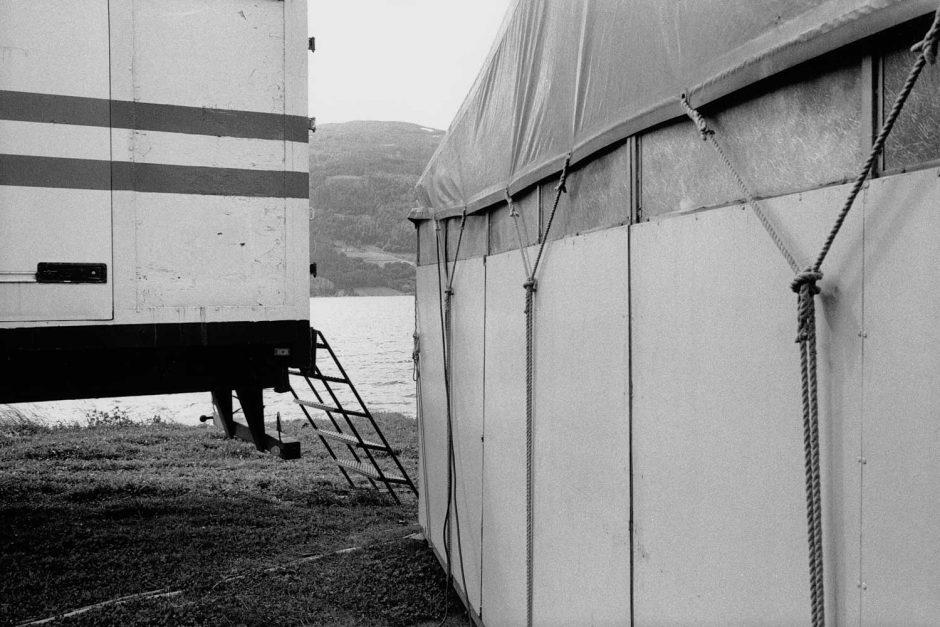 Zwart-wit foto van een tent en een kermiswagen