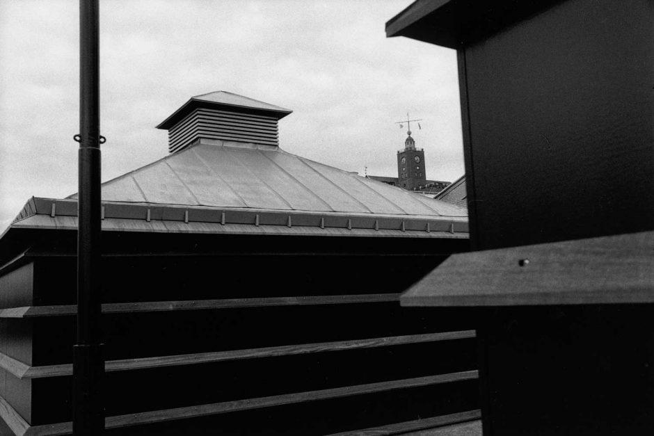 Zwart-wit foto van een kleide kerktoren tussen andere gebouwen