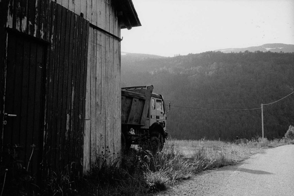 Zwart-wit foto van een vrachtwagen deels verscholen achter een oude schuur
