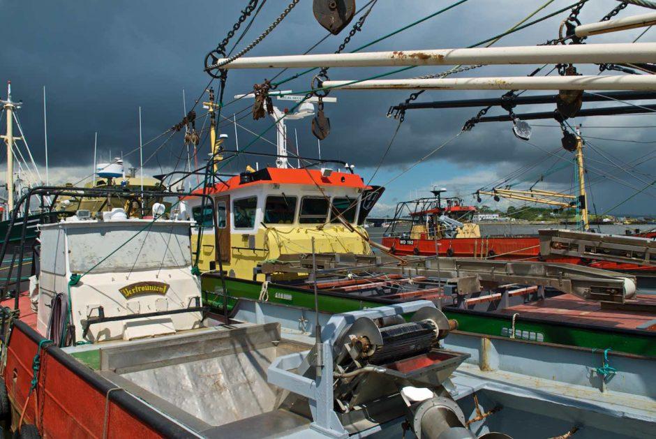 Kleurfoto van een marinehaven met fel gekleurde boten onder een dreigende hemel