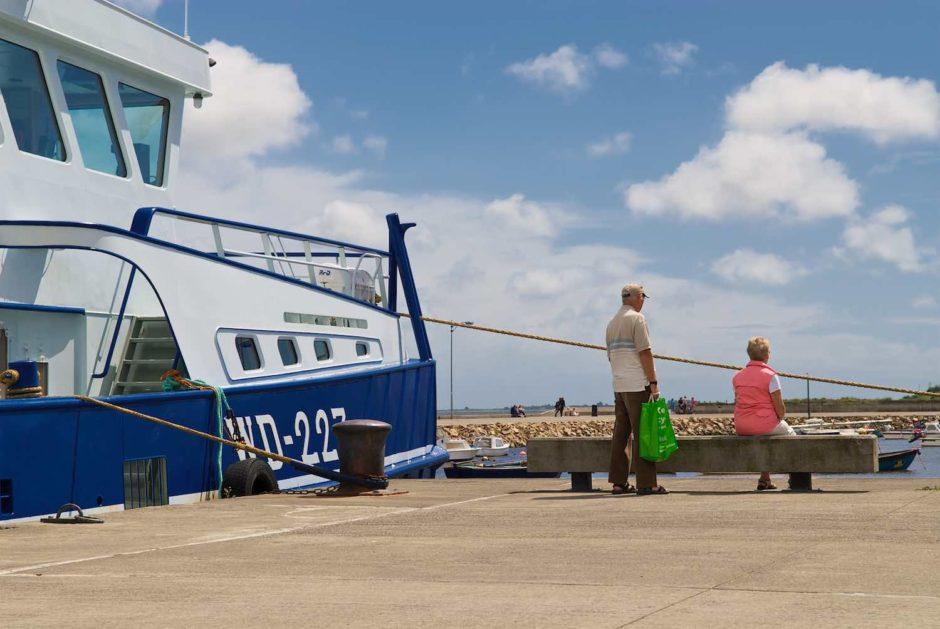 Kleurfoto van een koppel met groene draagtas en roze bodywarmer in een haven