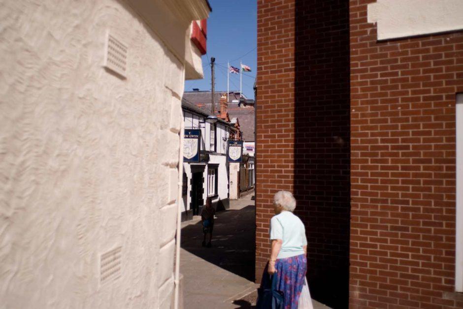 Kleurfoto van een oudere dame die door een smalle straat wandelt