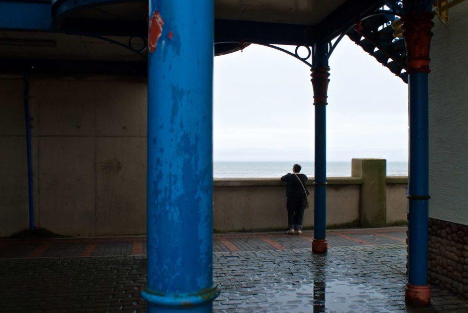 Kleurfoto van een dame die mijmerend over de zee uitkijkt