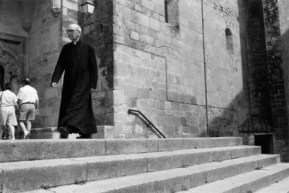Zwart-wit foto van een priester op de trappen van zijn kerk