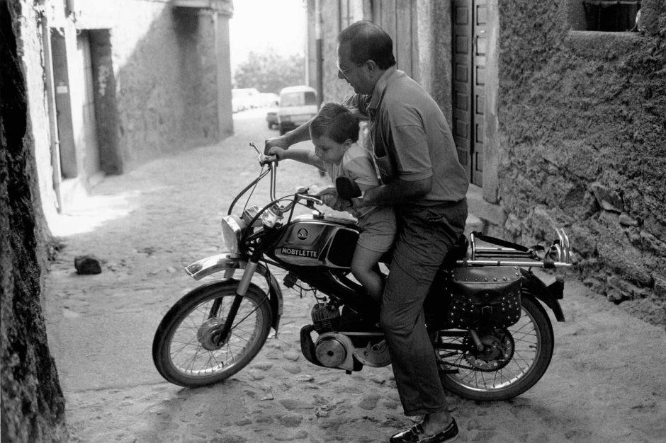 Zwart-wit foto van een oudere heer die een jongetje laat meerijden op de brommer
