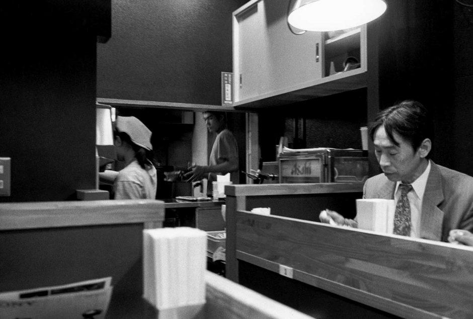 Zwart-wit foto van een man in noodle bar met op de achtergrond de kok