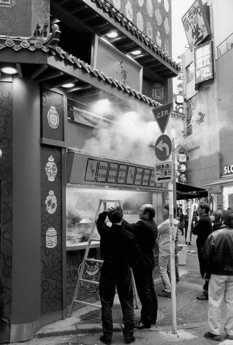 Zwart-wit foto van een eetkraampje waar rook uit ontsnapt