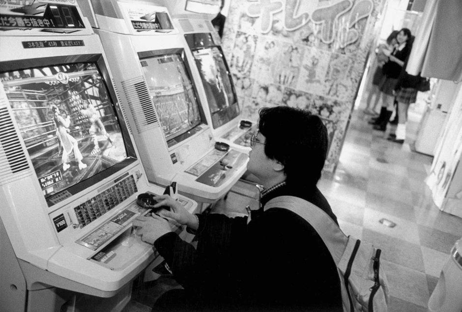 Zwart-wit foto van jongeren die videogames spelen in een lunapark