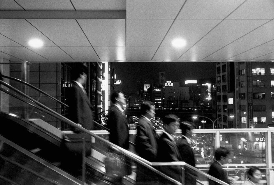 Zwart-wit foto van pendelaars op de roltrap in een metrostation