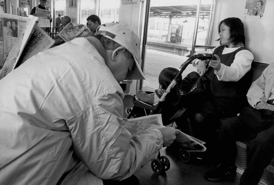 Zwart-wit foto van treinreizigers die de krant lezen