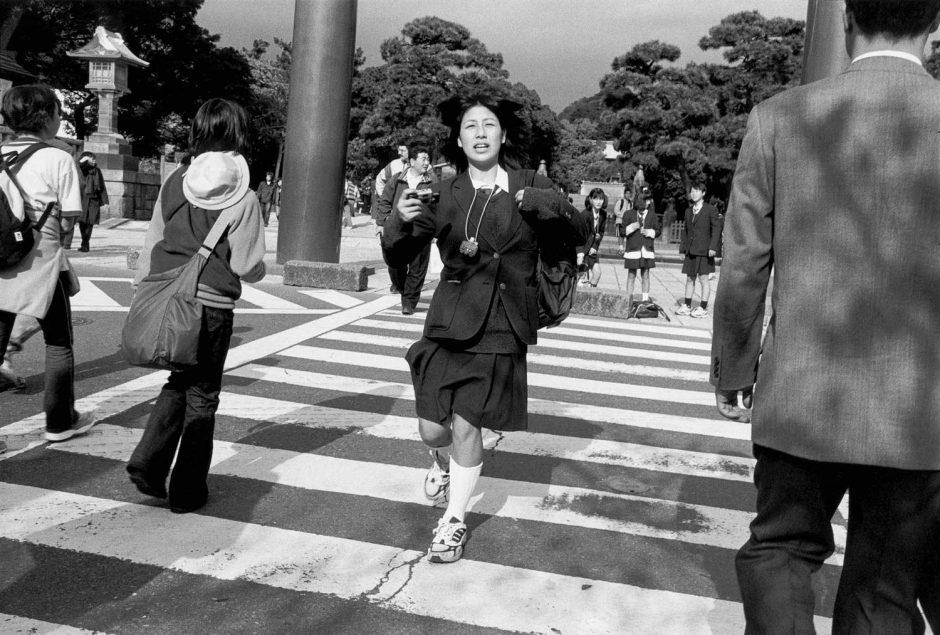 Zwart-wit foto van een tienermeisje in schooluniform dat over het zebrapad rent