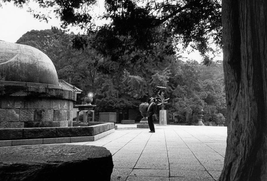 Zwart-wit foto van een man die zijn ogen beschermt en opkijkt naar de grote buddha