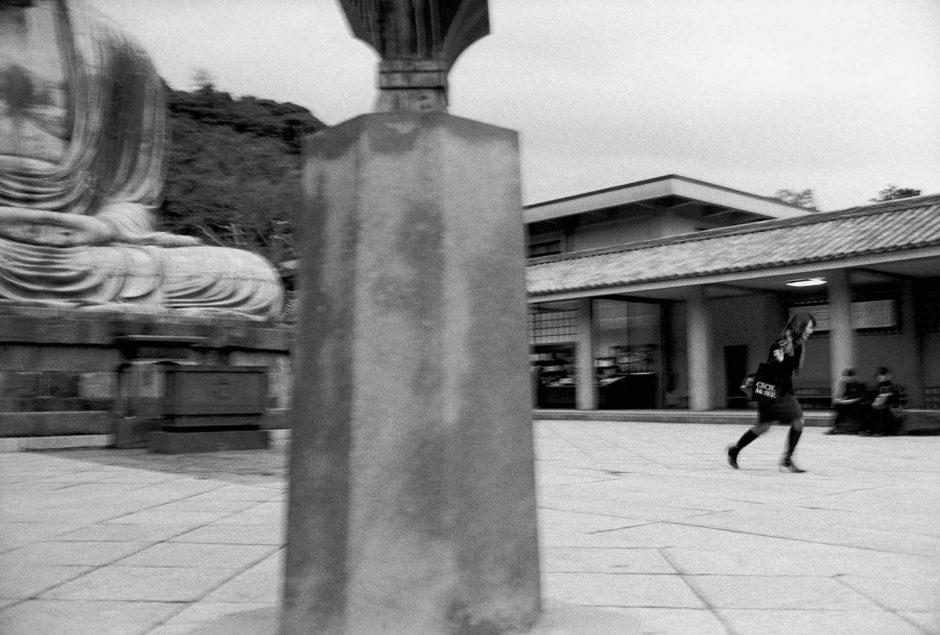 Zwart-wit foto van een jongedame die wegloopt van de grote Buddha in Kamakura