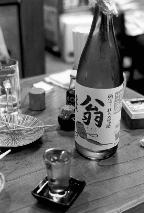 Zwart-wit foto van een geopende fles sake en een vol glaasje