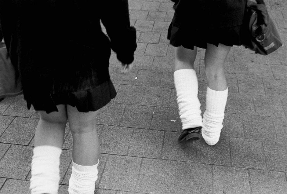 Zwart-wit foto van schoolmeisjes met beenverwarmers en plooirokjes