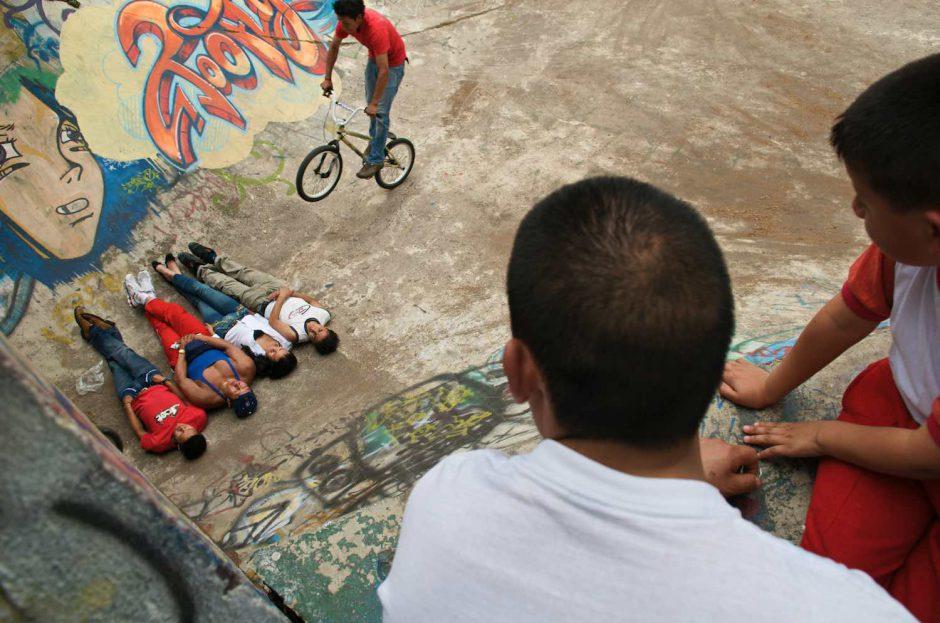 Kleurfoto van een stuntbiker die over 4 liggende mensen heen springt