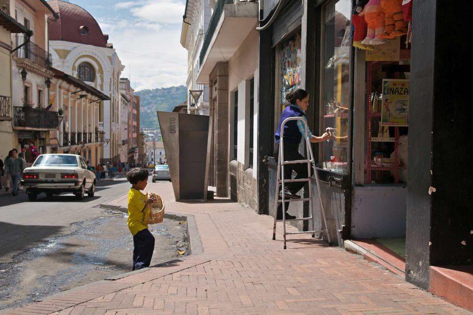Kleurfoto van een jongedame die ramen lapt in het historisch centrum van Quito