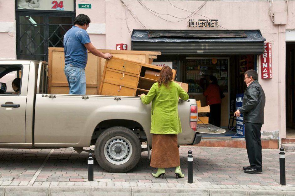 Kleurfoto van mensen die meubilair lossen uit een verhuiswagen