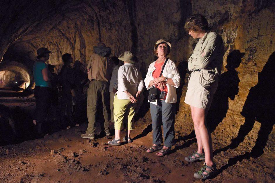 Kleurfoto van een toeristen aan de praat in de lavatunnels van Isla Isabela
