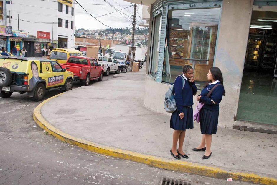 Kleurfoto van twee schoolmeisjes in uniform langs de kant van de weg