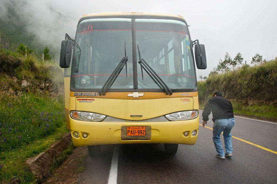 Kleurfoto van een gele bus die met motorpech lang de kant staat