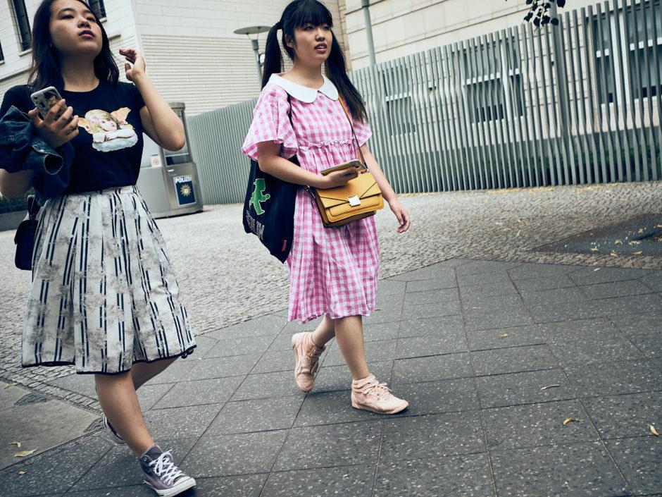Kleurfoto van 2 jonge dames waarvan eentje gekleed in een retro kleedje.