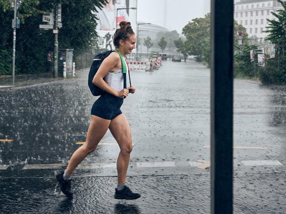 Kleurfoto van een jonge dame die in zomer outfit door de regen rent