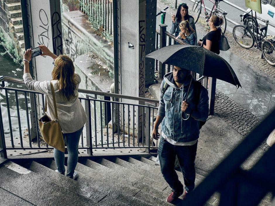 Kleurfoto van een jongeman met paraplu in een metropassage