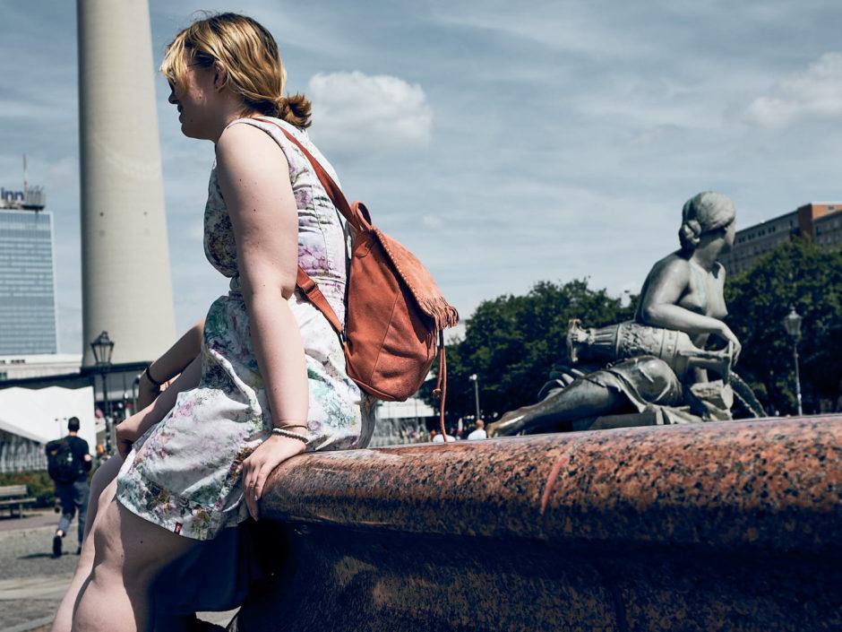Kleurfoto van een jonge dame met het haar opgestoken, net zoals het beeld op de achtergrond