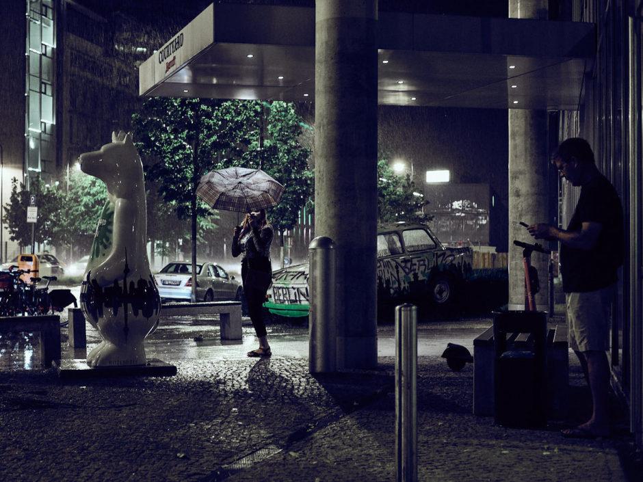 Kleurfoto van een dame in de regen bij nachte