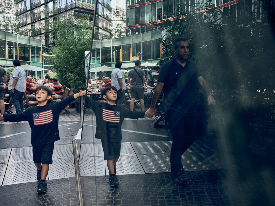 Kleurfoto van de reflectie van een jongetje aan de hand van zijn vader