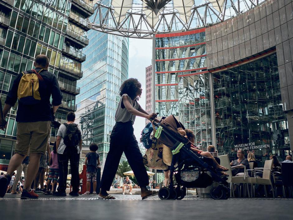 Kleurfoto van een jonge moeder met buggy aan het Sony Centre