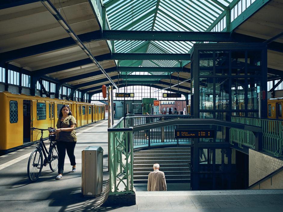 Kleurenfoto van een dame met fiets in een treinstation