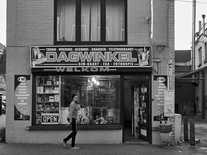 Zwart-wit foto van een jonge dame voor de gevel van een dagwinkel in de Phoenixstraat in Gent