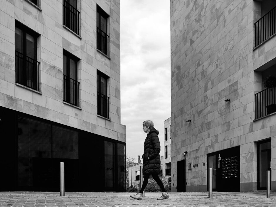 Black & white street photography of homo urbanus, more precisely a lady in between two housing blocks