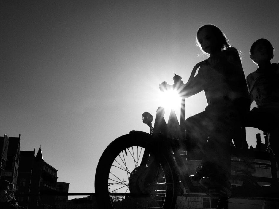 Black & white street photography of homo urbanus, more precisely of two youngsters on a tandem bike in back light