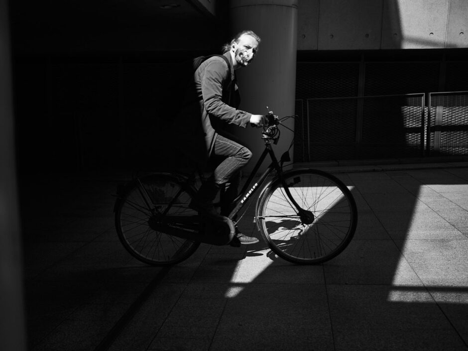 Black & white street photography of homo urbanus, more precisely of a young man on a bike entering the image in a beam of light