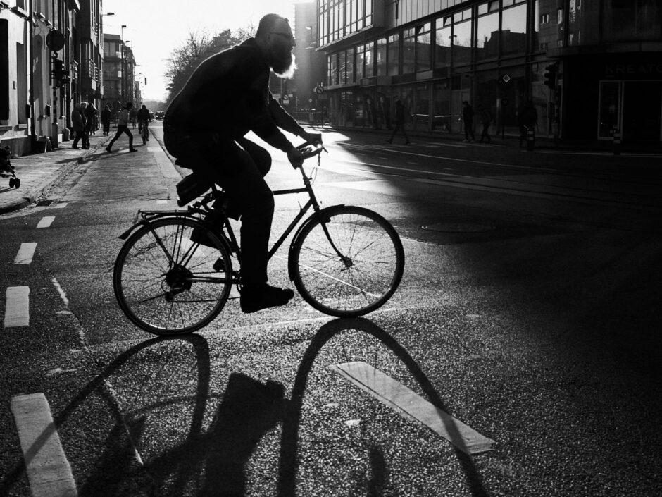 Black & white street photography of homo urbanus, more precisely of a bearded cyclist in back light sunburst