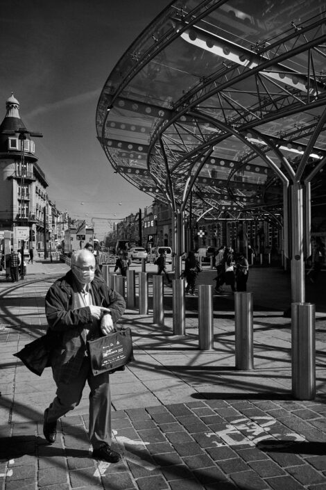 Black & white street photography of homo urbanus, more precisely of a man looking at his watch in front of a train station