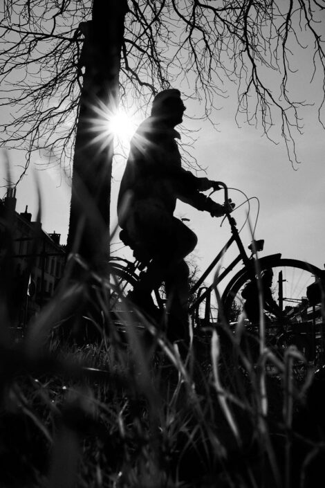Black & white street photography of homo urbanus, more precisely of a man on a bicycle in back light sunburst
