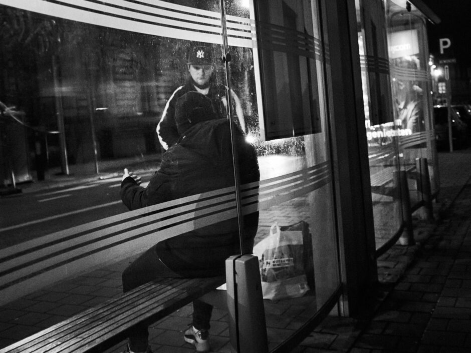 Black & white street photography of homo urbanus, more precisely of two guys waiting for the bus at night