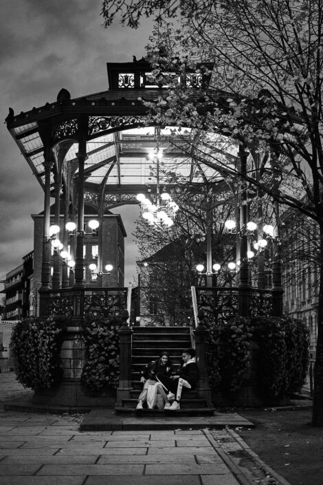 Black & white street photography of homo urbanus, more precisely of two youngsters at the foot of a music kiosk at dusk.