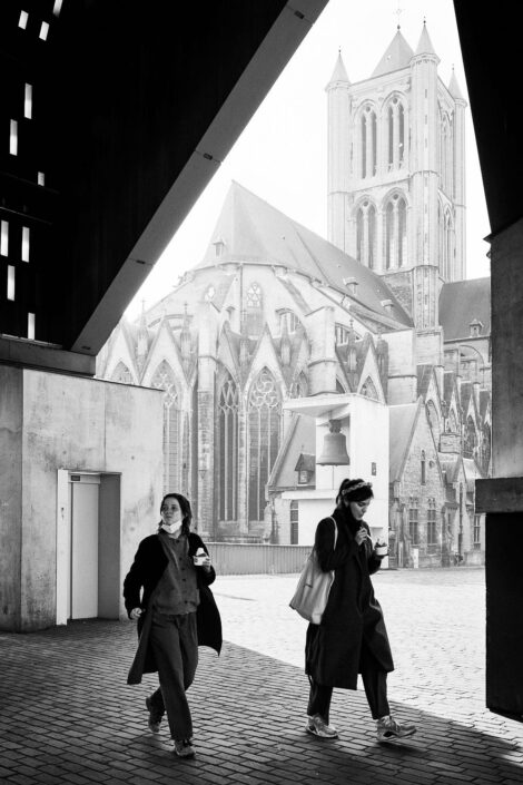 Black & white street photography of homo urbanus, more precisely of two young women with an ice-cream in front of the St Nicholas' Church in Ghent