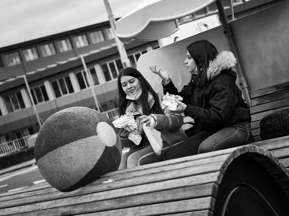 Black & white street photography of homo urbanus, more precisely of two young women enjoying a quick snack