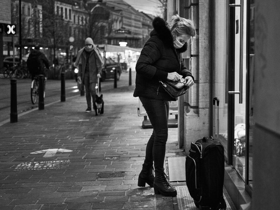 Black & white street photography of homo urbanus, more precisely of a young woman with a suitcase at the front door of a house at dusk