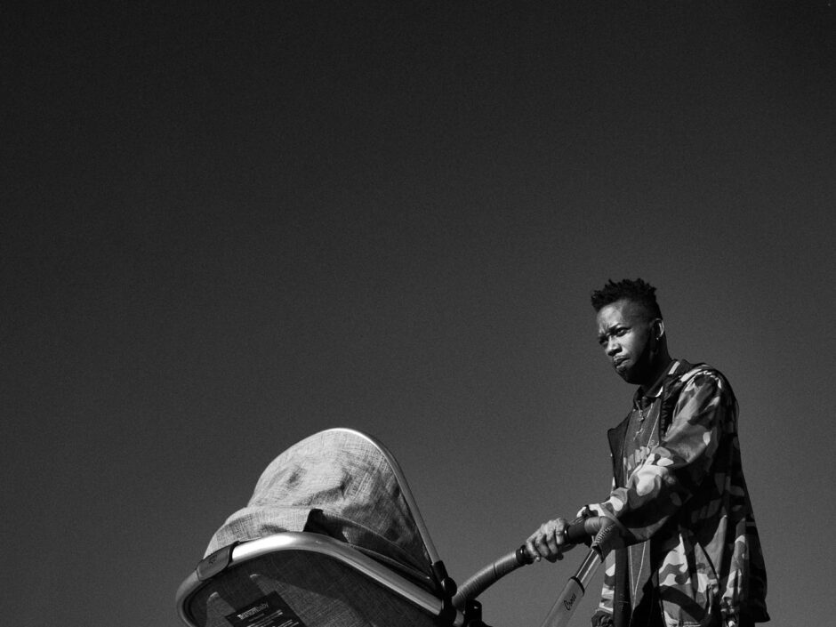 Black & white street photography of homo urbanus, more precisely of a young father pushing his pram in front of a blue sky backdrop